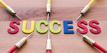 "The word ""Success"" pointed to by the tips of darts."