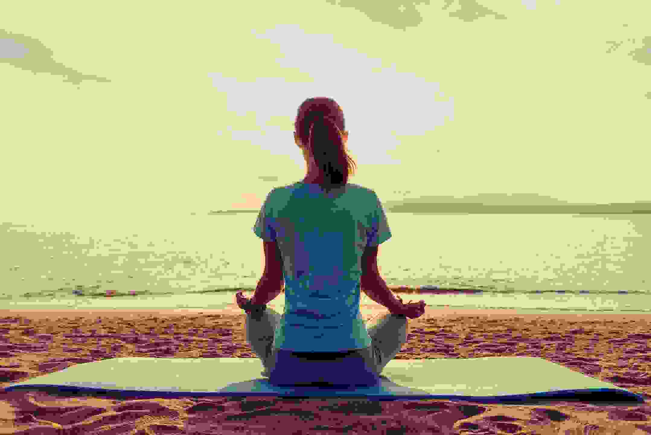 Woman shown meditating in yoga class on Negril Seven Mile Beach.