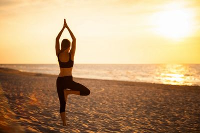 Woman doing yoga tree pose on a beach at sunrise