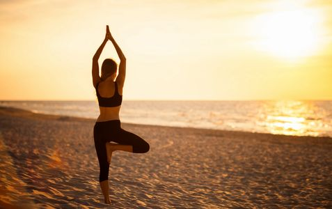 Woman doing yoga pose on a beach.  Healthy wholesome living being well enhancing wellness meditation