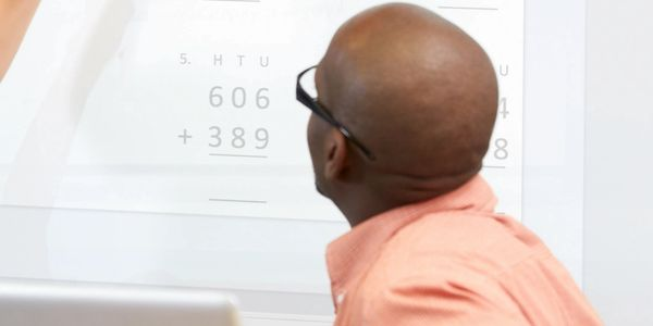 Man looking at board with math equations written on it
