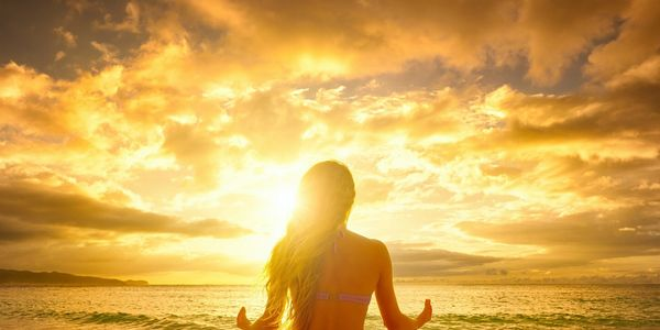 Women sitting in yoga pose looking in to sunrise showcasing calmness