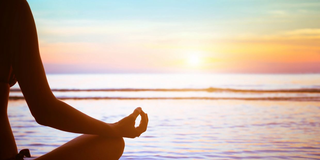 Photo of only right side of a woman sitting in a meditation position looking out onto a beautiful calm body of water.