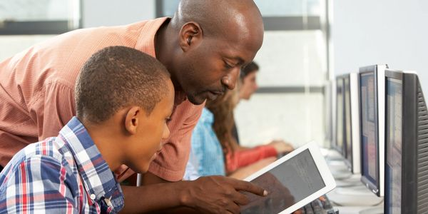 Teacher showing the tablet to the pupil