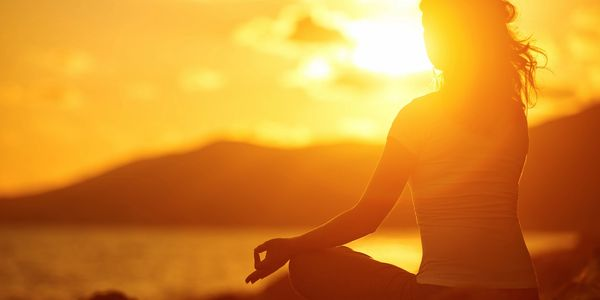 A woman meditating in front of a bright sunset. Nashville, Mama Moon, relaxation, Prenatal wellness