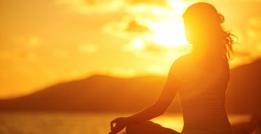 woman meditating in lotus pose at sunrise