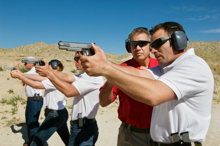 People shooting handguns at an outdoor range.