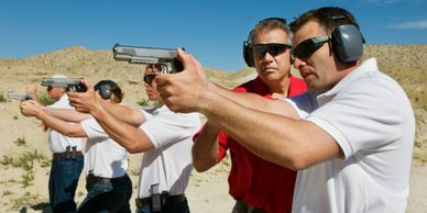 Men in shooting practice with handguns at a field
