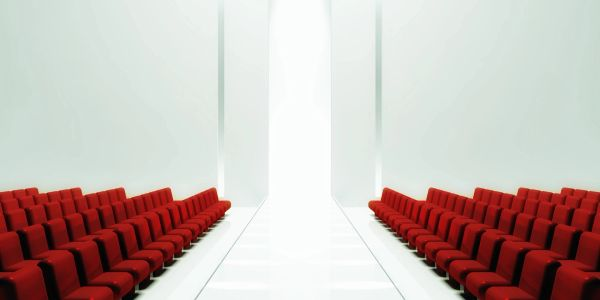 Kirsten Turkington speaker large conference room with red chairs and central walkway.