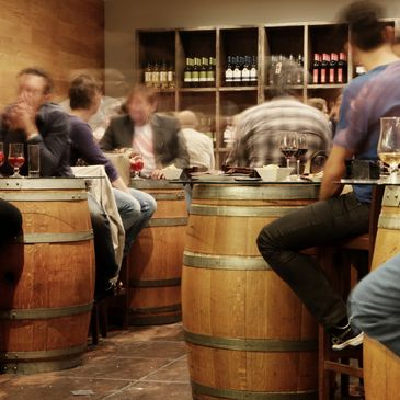 people sitting at wine barrel tables in a Tasting Room
