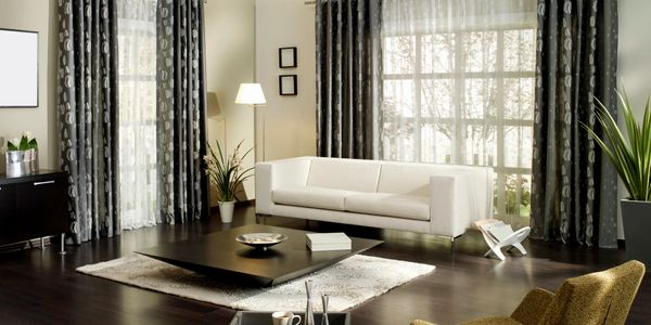 Living room with new cream colored interior paint, blue heavy long curtains and a white sofa