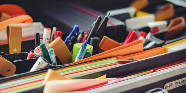 Box of office supplies such as pens, paper, pencils, and highlighters