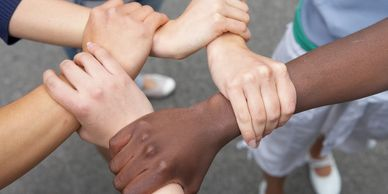 Five multiracial hands linking palms to wrists creating a shape
