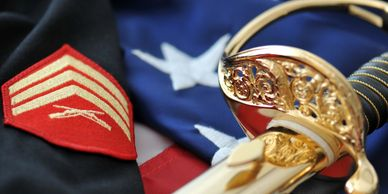 Marine Corps uniform with sergeant strips and NCO sword laid on top of the American flag