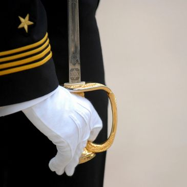 Dress Blue uniform with a sabor sword on the side