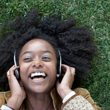 A woman is lsmiling while listening to something on headphone, lying on the grass in summertime.