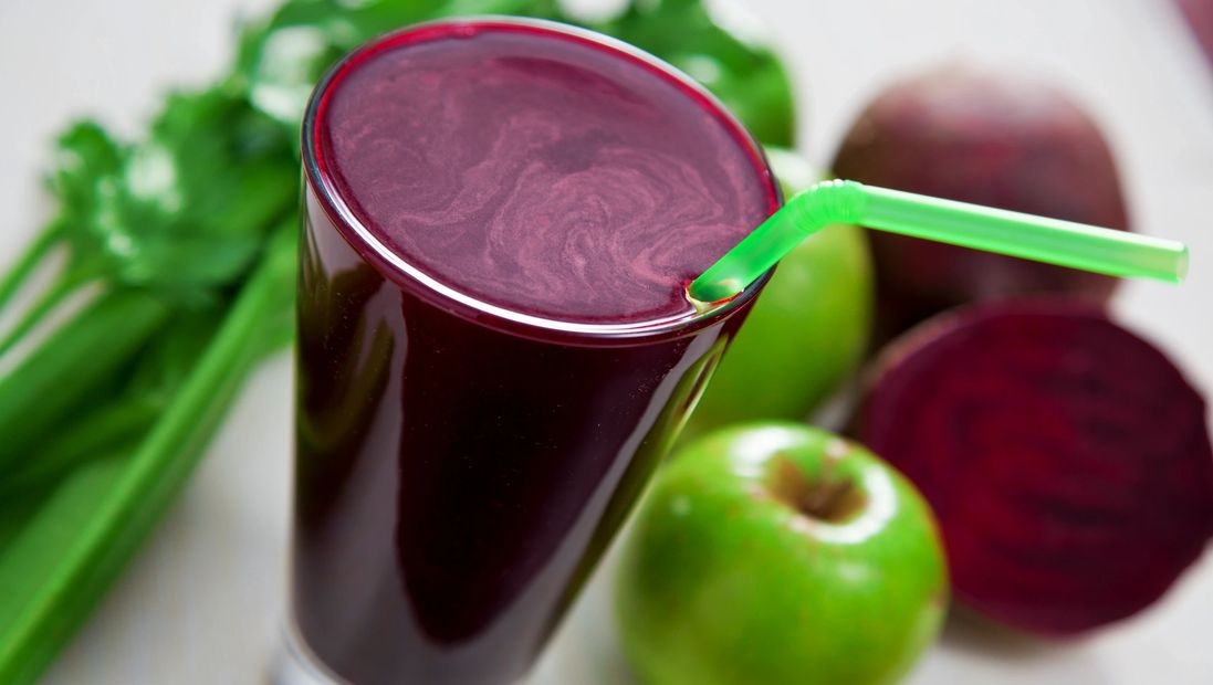 Photo of dark burgundy coloured smoothie in a glass, with beets, apples and celery in the background