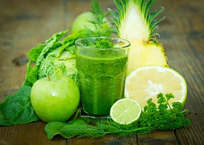 Green Smoothies are  packed with nutrition. An image of a green smoothie with an apple, greens, a le