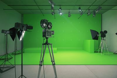movie camera and professional lighting in front of green screen