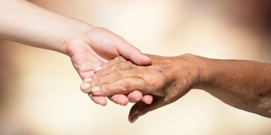 A younger person giving a helping hand to an elderly person