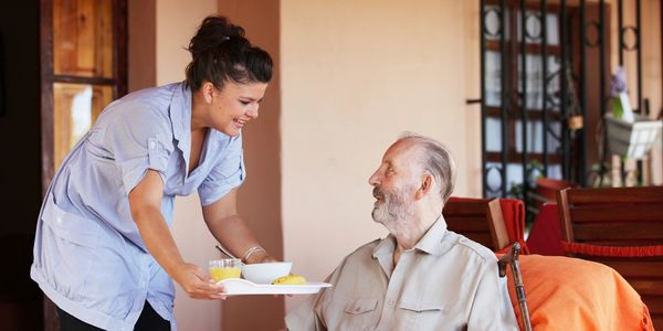 Home Health Aide brings a meal to a patient.