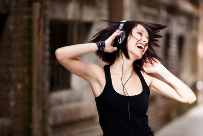 A happy girl, listening music on her headset.
