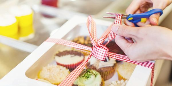 Packaged baked goods and cupcakes in a box with ribbon.