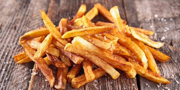 french fries golden brown and salted on a wood board
