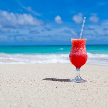 Red cocktail drink on beach sand near ocean