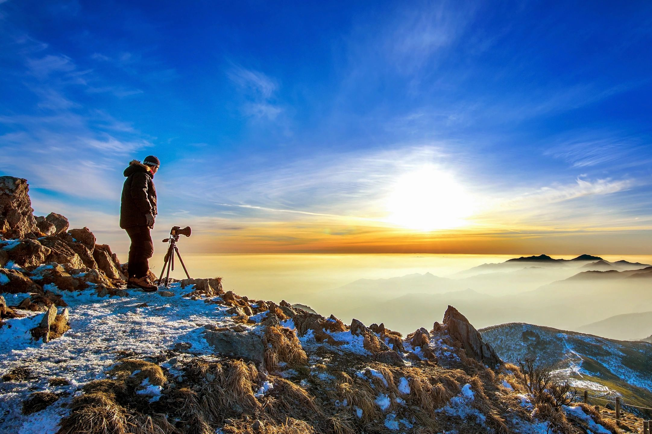 Man with tripod camera on top of a mountain looking out into infinity