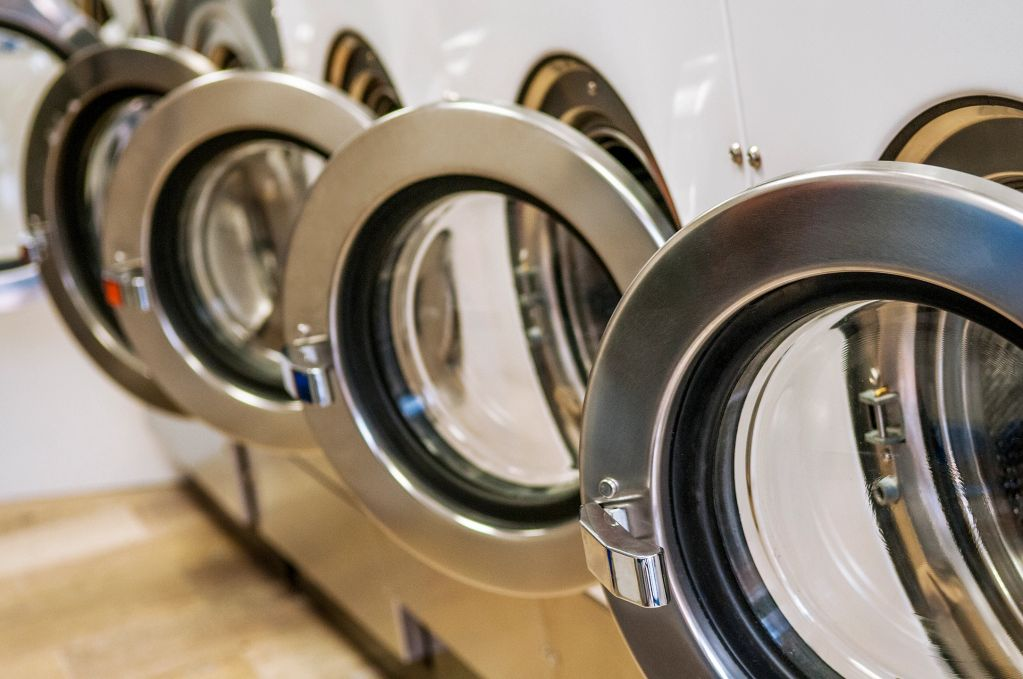 Row of front load washers in a commercial laundry facility.