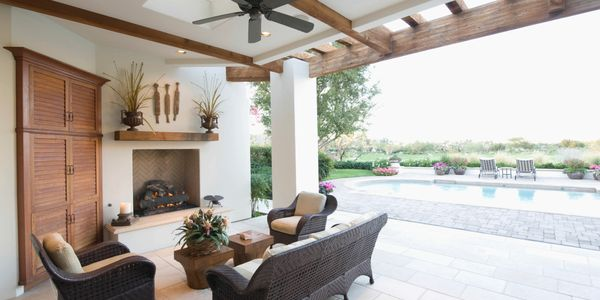Comfortable outdoor seating area with fireplace and pergola looking at picturesque in-ground swimming pool.