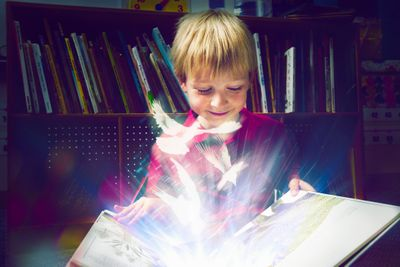 child opening a book with magical lights dancing invite you to discover our restful, energizing mp3s