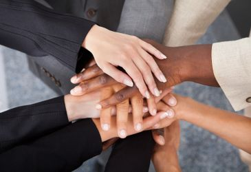 Team of 4 people placing their hands together in the middle to signify team support.