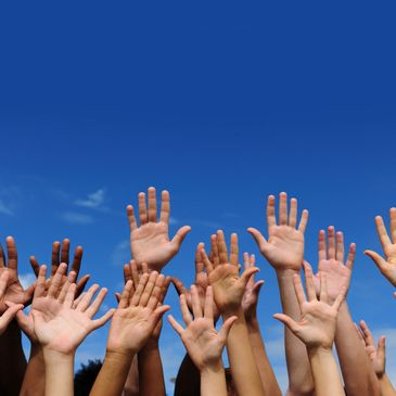 For screen readers: an image of numerous hands of various skin tones reaching up to volunteer