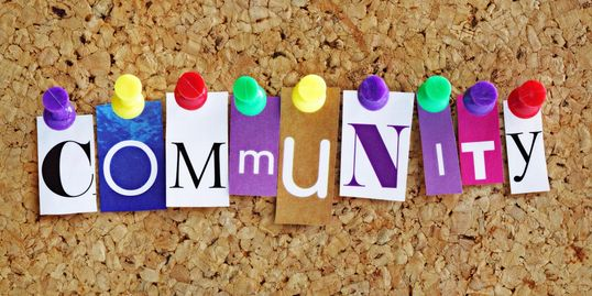 The word Community spelled out in letters tacked onto a board.