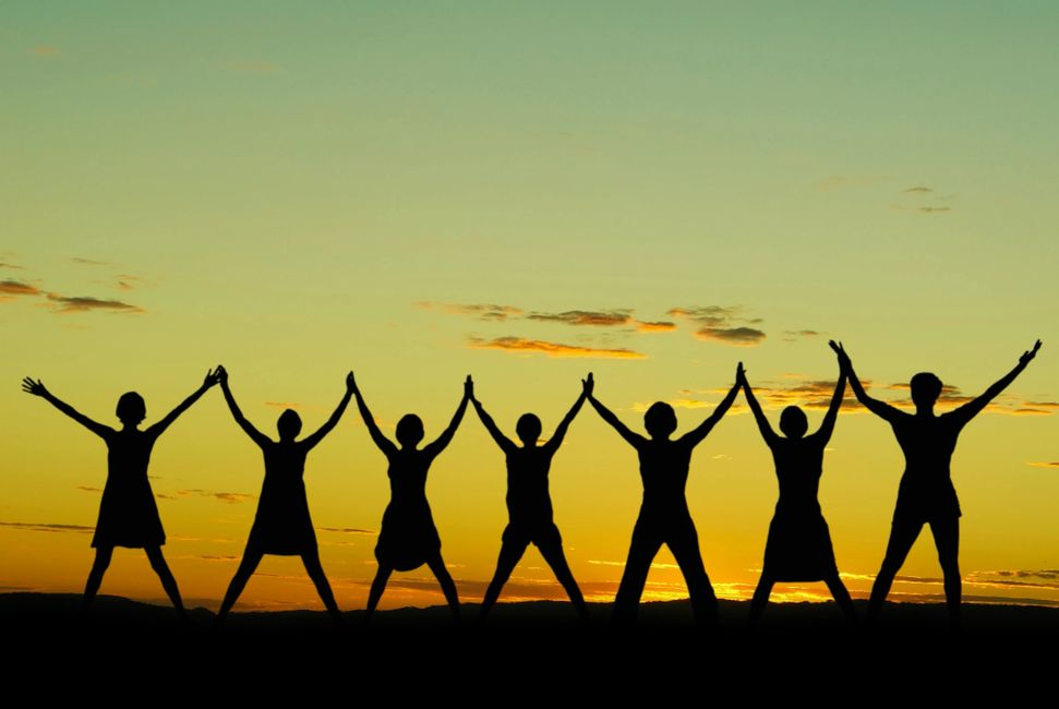 Young people standing in the sunset with their hands raised to the sky