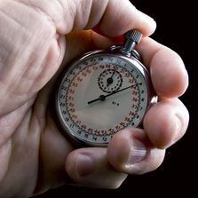 Image of hand holding a round stop watch indicates control of time with the Angle-Rite clamp.