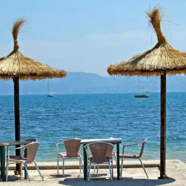 table and chairs overlooking a beach and the sea with parasols and boats
