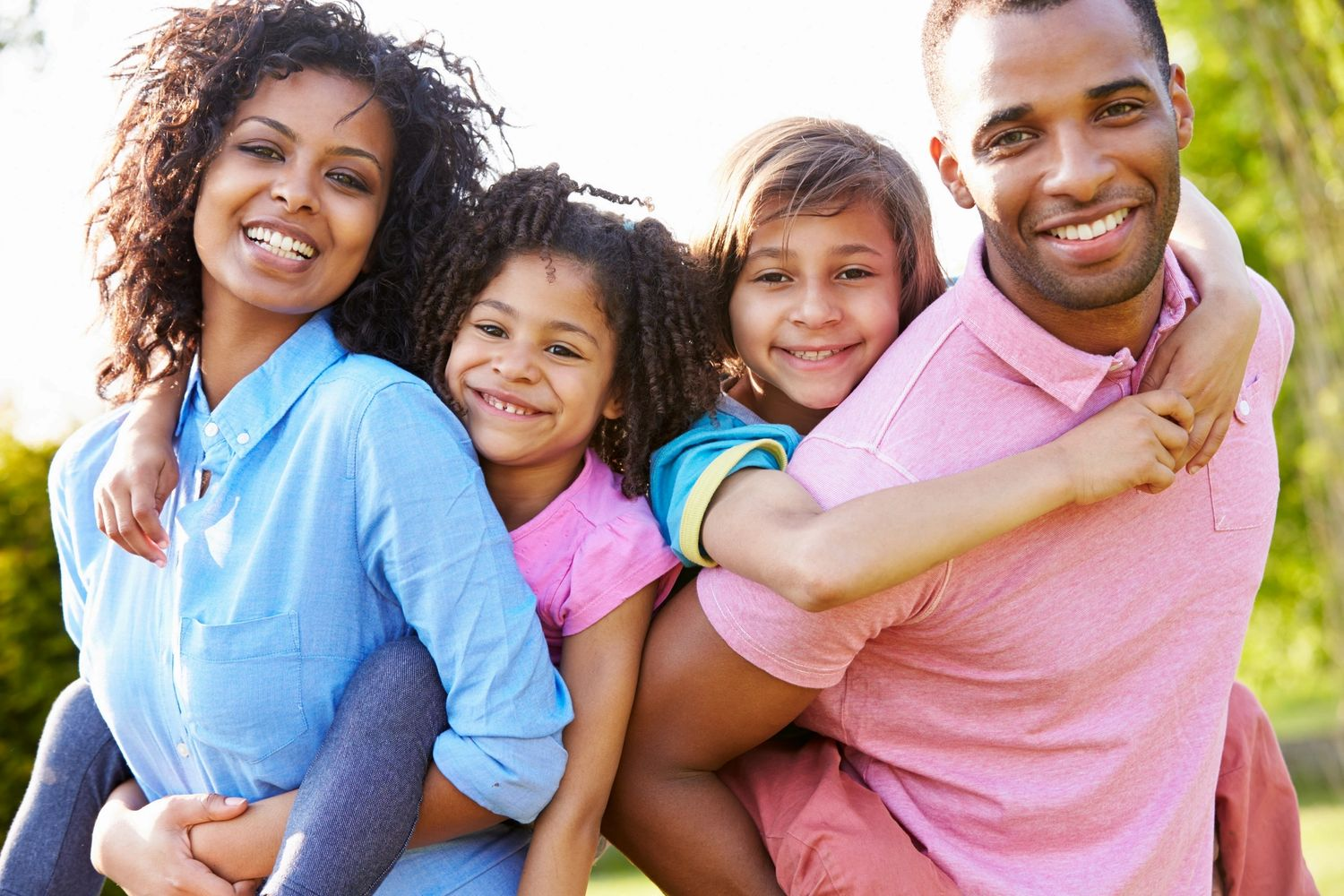 A family of four smiling ready for chiropractic care. Chiropractic care for the entire family.