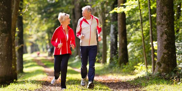 Picture of elderly couple on a wooded park walking trail enjoying a beautiful day & benefits of CBD!