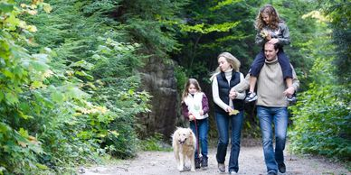 Family walking with their dog in nature.