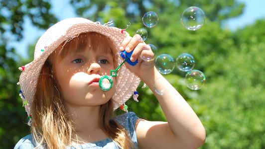 Young girl blowing bubbles outside during the daytime in the sunshine with nice weather