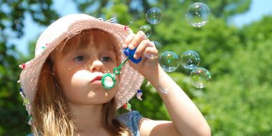 little girl outside, blowing bubbles with a bubble wand
