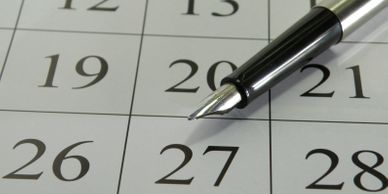Close up image of a calendar with an ink pen laid across it.