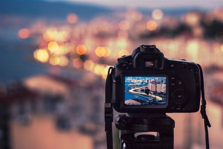 Image of camera taking a photo of city skyline. Photo Consulting.