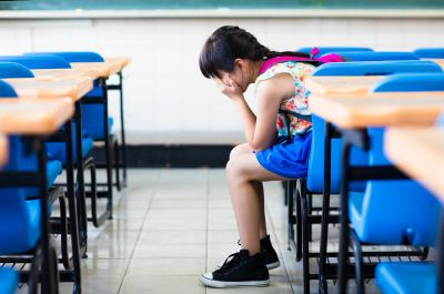 For screen readers: an image of an Asian child crying at her school desk alone with her face covered