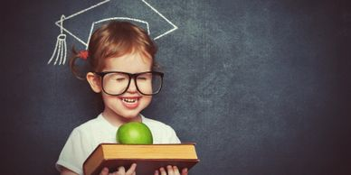 Happy child with an apple and book in his hands aiming for higher education.