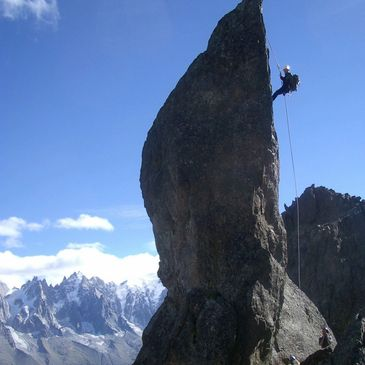 A person abseiling down a mountain with other mountains in the background.