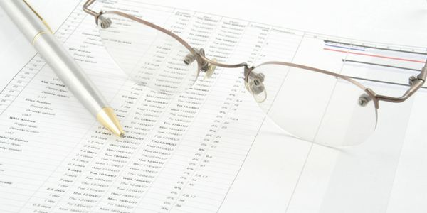 A picture of a pair of glasses and a pen on a report